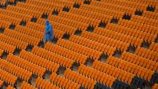 A lone man wearing a poncho walks through empty stands at Soccer City stadium in Johannesburg. Photo: AP Photo/Rebecca Blackwell