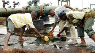 Nigerians scooping spilled crude oil from the Bomu flow station at Kedere in Ogoniland in the Niger Delta. File picture: George Esiri/Reuters