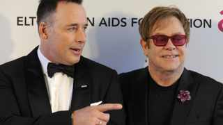 Musician Elton John and his partner David Furnish, who have two children via a surrogate mother.
