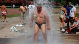 File image: A man cools off under big shower, in Marseille, southern France. AP