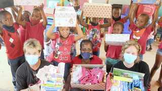 Margie Kostelac and Lee-Ann Raaff of Santa Shoebox Project, and principal at Kameeldrift Early Learning Centre Lilly Ledwaba, with some of the children during the handover of gifts donated in partnership with the Ford Motor Company of Southern Africa. Picture: Jacques Naude/African News Agency (ANA)