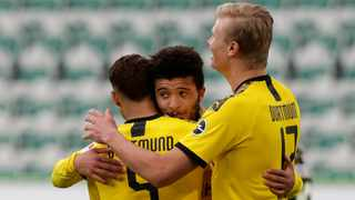 Dortmund's Achraf Hakimi, left, celebrates with Jadon Sancho and Erling Haaland, right, after scoring his side's second goal during their German Bundesliga match against VfL Wolfsburg in Wolfsburg on Saturday. Photo: Michael Sohn/AP