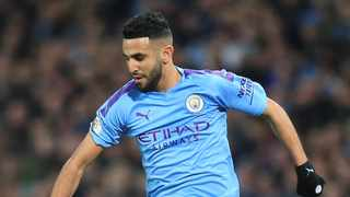 """(FILES) In this file photo taken on December 29, 2019 Manchester City's Algerian midfielder Riyad Mahrez controls the ball during the English Premier League football match between Manchester City and Sheffield United at the Etihad Stadium in Manchester, north west England. - Mahrez kicked the ball in every corner of his city in Sarcelles, a suburb of Paris, which he decided to leave at the age of 18 without joining a training center. The """"Sarcelles nugget"""" Riyad Mahrez owes his career and his success to his self-sacrifice. (Photo by Lindsey Parnaby / AFP)"""