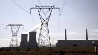 Electricity pylons are seen near the cooling towers of a power station owned by state power utility Eskom. File Picture: Siphiwe Sibeko/Reuters