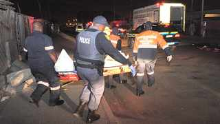Police collect bodies from one of the crime scenes in Philippi East. Picture: Leon Knipe