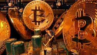 A small toy figure and representations of the virtual currency Bitcoin stand on a motherboard. File picture: Reuters/Dado Ruvic