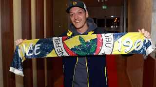 German midfielder Mesut Ozil poses with a Fenerbahce scarf upon his arrival at Ataturk Airport in Istanbul last week. Photo: Fenerbahce.org/Reuters