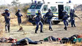 A policeman gestures in front of some of the miners who were shot outside Lonmin's Marikana mine in the North West. File photo: Siphiwe Sibeko/Reuters