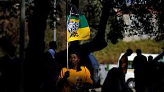 A woman holds an ANC flag. The writer says the party is sinking into an abyss. Picture: Reuters