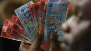 A man holds Ghana's cedi notes in Accra in this file picture.