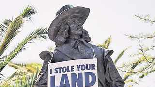 Placards hang around the necks of the statues of Jan van Riebeeck and his wife Maria de la Quellerie in the CBD. Picture: David Ritchie/African News Agency (ANA)
