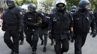 Police officers in Berlin, Germany, detain Attila Hildmann during a rally against the government's restrictions following the coronavirus disease outbreak. Picture: Christian Mang/Reuters