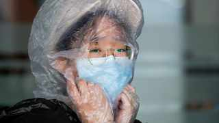 A Chinese woman uses a plastic bag to cover her head while waiting for her flight at the departure area of Manila's International Airport, Philippines on Wednesday, March 18, 2020. (AP Photo/Aaron Favila)
