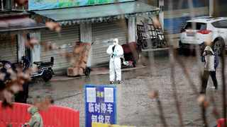 A worker in a protective suit is seen at the closed seafood market in Wuhan has been linked to the outbreak of the coronavirus. File picture: Reuters