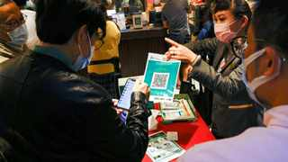 A staff member holds a QR code for the LeaveHomeSafe Covid-19 contact-tracing app to consumers at a restaurant. File picture: Reuters/Tyrone Siu