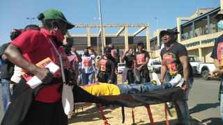 Undertakers protest in front of Chris Hani Baragwanath Academic Hospital. One protester lies on a body bag on a stretcher carried by two other protesters. Picture: Timothy Bernard. African News Agency (ANA)
