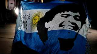 A soccer fan holds an Argentine flag with the face of late Argentine soccer legend Diego Armando Maradona painted on it during a tribute to him the day after his death, in Barcelona, Spain, November 26, 2020. Photo: REUTERS/Nacho Doce