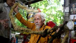 Nguyen Van Chien, 92, sits for a portrait to show his 5-metre long hair which, according to him, has not been cut for nearly 80 years. Picture: Yen Duong/Reuters