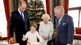 Britain's Queen Elizabeth, Prince Charles, Prince William and Prince George smile as they prepare special Christmas puddings in the Music Room at Buckingham Palace, London. Picture: Chris Jackson/Buckingham Palace via AP