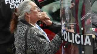 A relative of inmates reacts as she waits for news of her relative in front of police officer outside the state prison in Apodaca, on the outskirts of Monterrey.