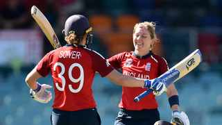 FILE - England's Heather Knight (R) celebrates reaching her century with a teammate Natalie Sciver during the Twenty20 women's World Cup cricket match. Photo: Peter Parks/AFP