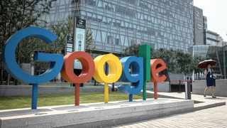 A woman walks next to a 'Google' brand name and logo, near the Google office in Beijing, China.