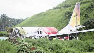 Officials stand on the debris of the Air India Express flight that skidded off a runway while landing in Kozhikode on Saturday. AP Photo/C.K.Thanseer.