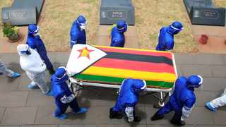Pallbearers in Harare, Zimbabwe, carry a coffin at the burial of two cabinet ministers and a retired general who died after contracting Covid-19. Picture: Philimon Bulawayo/Reuters