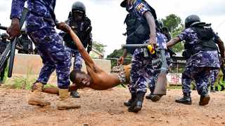 Ugandan riot policemen detain a supporter of presidential candidate Robert Kyagulanyi, also known as Bobi Wine, in Luuka district, eastern Uganda. Picture: Abubaker Lubowa/Reuters