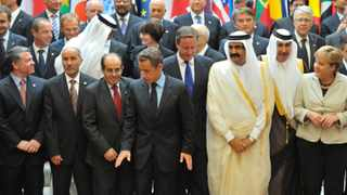 """Delegations pose for a family photo during the """"Friends of Libya"""" conference at the Elysee Palace in Paris."""