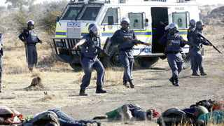 Policemen keep watch over striking miners after they were shot outside Lonmin's Marikana. Picture taken August 16, 2012. Picture: Siphiwe Sibeko/Reuters