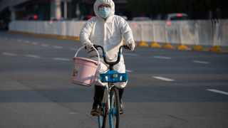 A resident wearing mask and suit against the coronavirus cycles in Wuhan. in central China's Hubei province. Picture: Ng Han Guan/AP