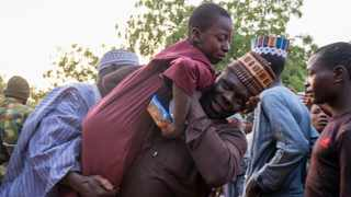 A man reacts as he reunites with his son who was among those who were kidnapped upon their release in Katsina, on December 18. Picture: Kola Sulaimon / AFP.