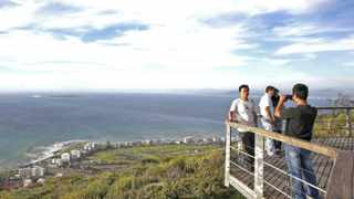 Tourists take pictures from a viewing platform overlooking Cape Town's Atlantic beachfront. Some countries are withdrawing South Africa from their tourism offerings - stating that it is simply becoming too expensive and laborious to get their clients here, says the writer. File picture: Mike Hutchings