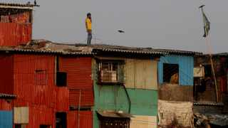 A boy stands on the roof of a house and speaks on a phone during a lockdown in Mumbai, India. Picture: AP Photo/Rafiq Maqbool