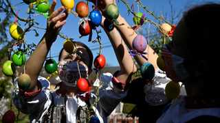 Vanda Mrazikova and Martina Kacenova, dressed in traditional costume with protective face masks, decorate a weeping willow with colored Easter eggs, amid the coronavirus disease (COVID-19) outbreak, in the village of Soblahov, Slovakia, April 7, 2020. REUTERS/Radovan Stoklasa