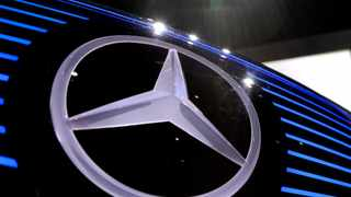 FILE- In this Feb. 2, 2017, file photo, the logo of Mercedes is photographed at the annual news conference at the company's headquarters in Stuttgart, Germany. Amazon.com Inc. is buying 1,800 electric delivery vans from Daimler AG's Mercedes-Benz, the retailer's biggest commitment to date to cut the carbon footprint of its delivery operations in Europe. (AP Photo/Matthias Schrader, File)