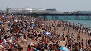 Beachgoers enjoy the sunshine and sea in Brighton on what is now Britain's hottest day of the year so far. Picture: Alastair Grant/AP