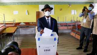 Ivory Coast President Alassane Ouattara wearing a face mask casts his vote at a polling station during the legislative election in Abidjan. Picture: Macline Hien/Reuters