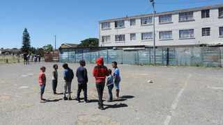 Children from the neighbourhood stand around the spot where Mikyle was robbed and stabbed to death on his 17th birthday in Parkwood. Picture: Armand Hough/African News Agency(ANA)