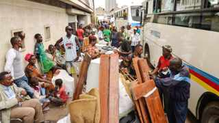 A file picture taken on April 29, 2014 shows people from the DRC waiting to board government-run buses as they arrive with their belongings from neighbouring Congo-Brazzaville after being forcefully deported, at Ngobila beach, near Kinshasa. Picture: JUNIOR D KANNAH