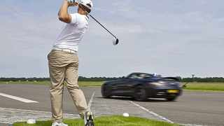 David Coulthard in the AMG SLS Roadster accelerates past golfer Jake Shepherd as the latter fires a mighty tee shot.