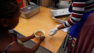 Volunteers and teachers serve food at a school feeding scheme in Gugulethu. File picture: Mike Hutchings/Reuters