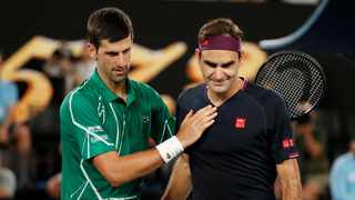 Novak Djokovic commiserates with Roger Federer following their match in Melbourne on Thursday. Photo: Issei Kato/Reuters