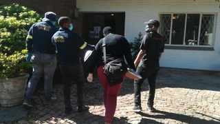 Hawks officers at one of the properties where 11 women were kept as sex slaves. Picture: Supplied.