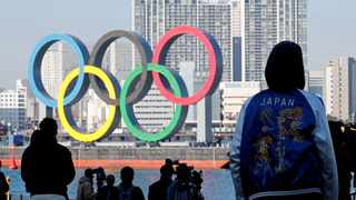 FILE - Bystanders watch as giant Olympic rings are reinstalled at the waterfront area at Odaiba Marine Park, after they were temporarily taken down in August for maintenance amid the coronavirus disease outbreak in Tokyo. Photo: Kim Kyung-Hoon/Reuters