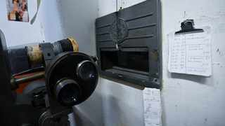 """A view taken shows a projector and a screenings' schedule (R) in the projection room of the """"Ambasciatori"""" (The Ambassadors), Rome's last porn cinema theater. Photo: Alberto PIZZOLI / AFP"""