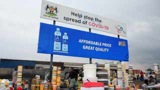 Containers and other goods are sold beneath a coronavirus awareness billboard at a marketplace in Harare. Picture: Philimon Bulawayo/Reuters