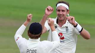 England's Stuart Broad, right, celebrates with teammate Ollie Pope following the dismissal of the West Indies' Roston Chase during the second day of the third Test at Old Trafford. Picture: Martin Rickett/Pool via AP