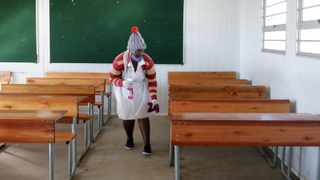 Ntombi Majola sanitises desks at Dlulumuzi high school KwaXimba as pupils learn of two week delay to start of school term. Picture: Bongani Mbatha/ Africa News Agency (ANA)
